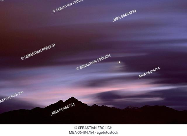 Unique night photography with beautyful clouds and sickle moon over the Nockspitze