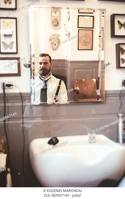 Mirror image of male client in barber shop