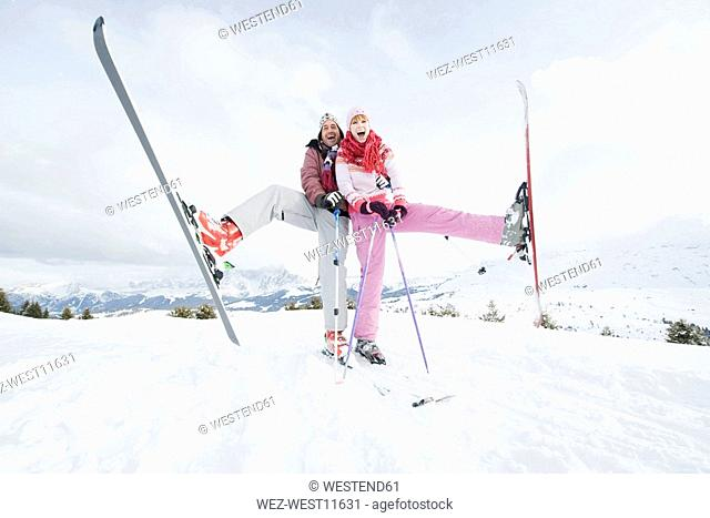 Italy, South Tyrol, Seiseralm, Couple standing on skis, lifting leg
