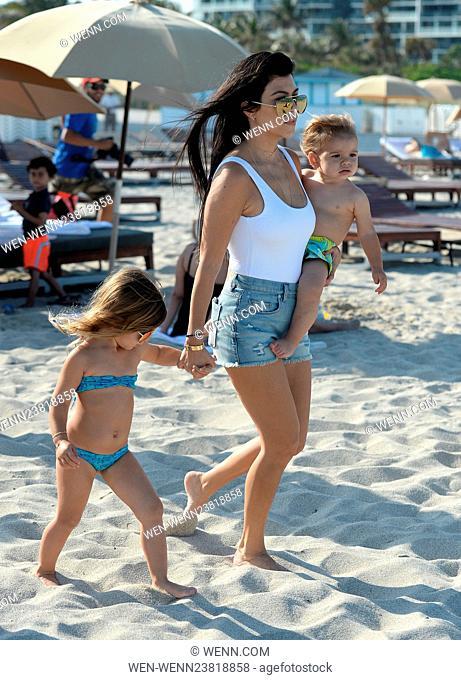 Kourtney Kardashian wears a white one piece swimsuit and denim hotpants as she takes her kids to the beach in Miami Featuring: Kourtney Kardashian, Reign Disick