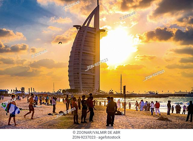 Dubai, United Arab Emirates - December 2, 2014: Many tourists on the Jumeirah Marina beach during a sunny day. The famous and luxury hotel Burj Al Arab is...
