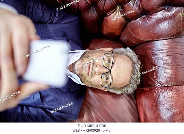 Mature businessman lying down looking on cell phone