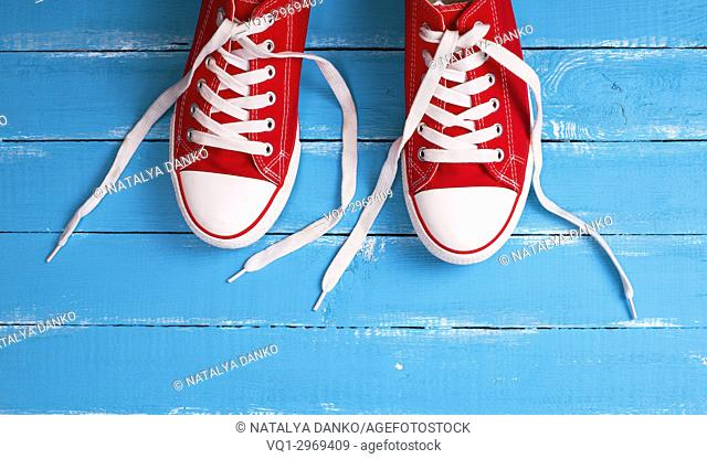 pair of red textile sneakers with white laces on a blue wooden background, top view, empty space