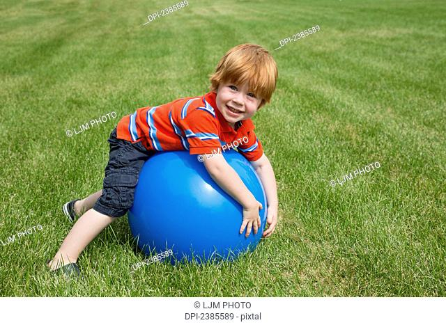 A young boy with red hair plays with a large blue ball on the grass; Stony Plain, Alberta, Canada