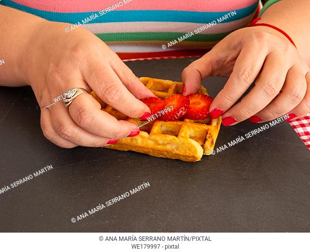 A woman with red fingernails placing strawberry pieces on a Belgian waffle