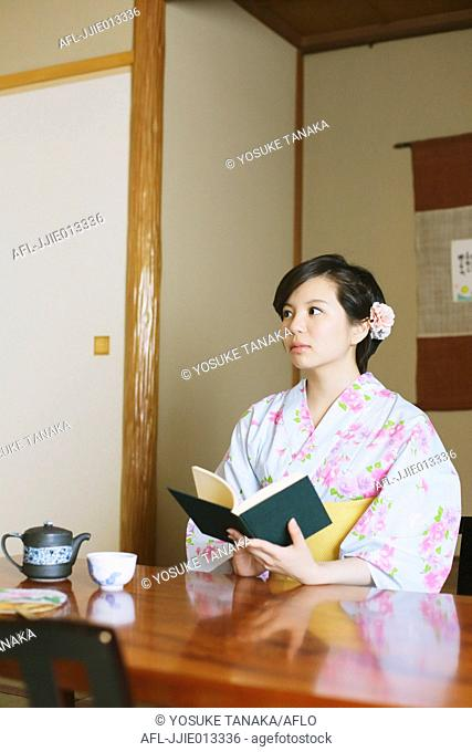 Young Japanese woman in a yukata reading a book
