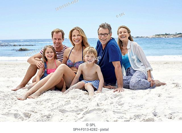 MODEL RELEASED. Three generation family sitting on the beach, portrait