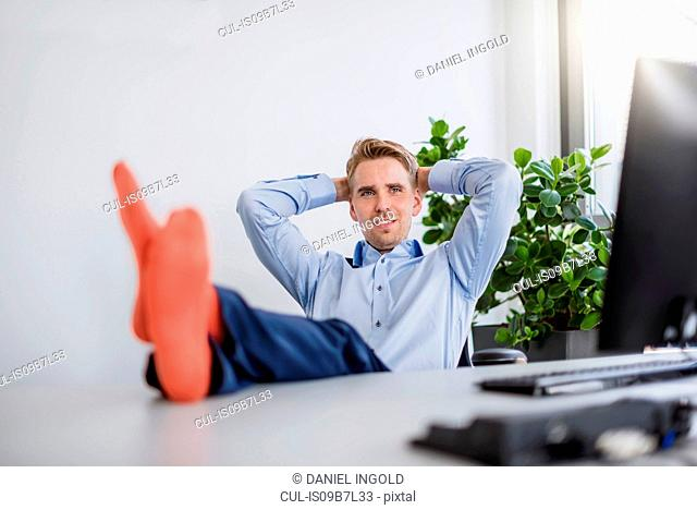 Portrait of confident mid adult businessman with socked feet up on desk