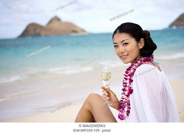 A young woman holding wineglass sitting at beach