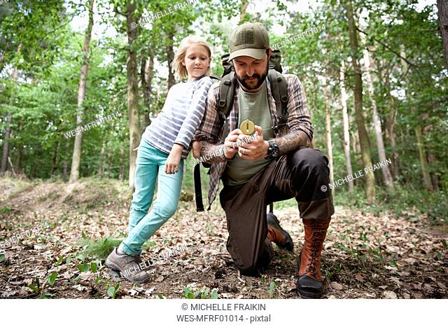 Father and daughter with compass in forest