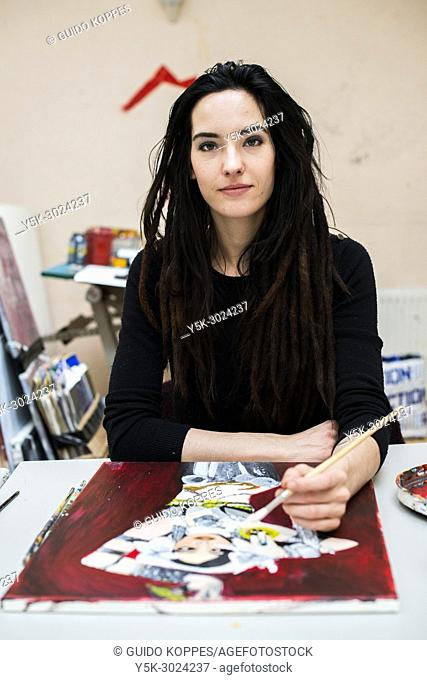 Rotterdam, Netherlands. Female artist at Via Kunst Art Studio working on a painted portrait