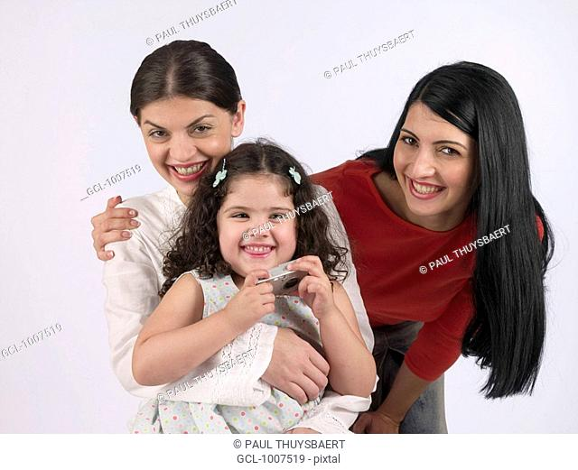 Two women and a child holding a camera