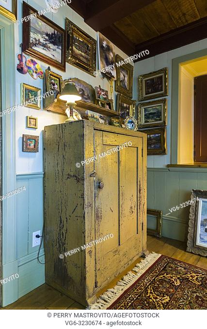 Artist's upstairs studio with paintings on the walls plus antique wooden ocre armoire inside an old circa 1805 Canadiana cottage style home