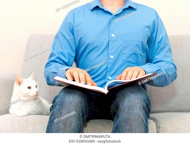 Blind man reading braille book on the couch