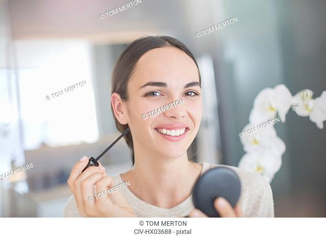 Portrait smiling, confident woman applying mascara with mascara wand and compact mirror