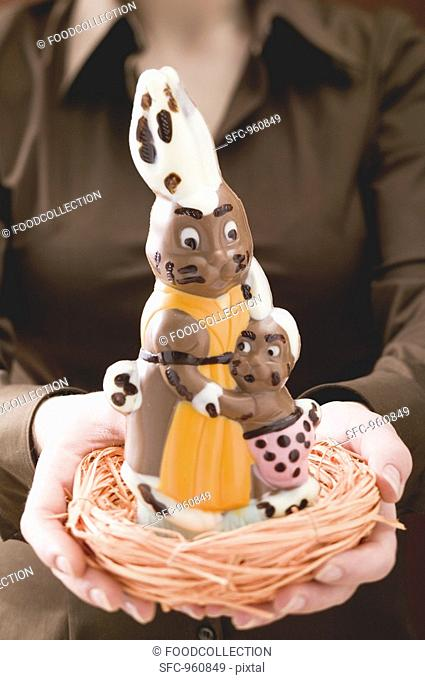 Woman holding chocolate bunnies in Easter nest