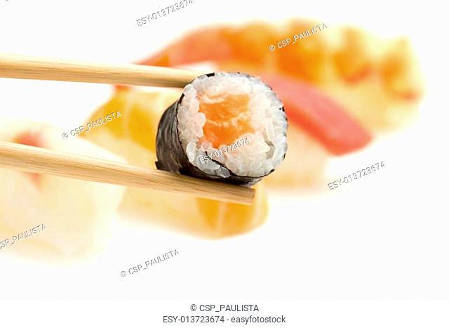 chopsticks with salmon sushi roll