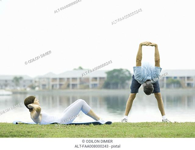 Mature couple exercising, lakeside