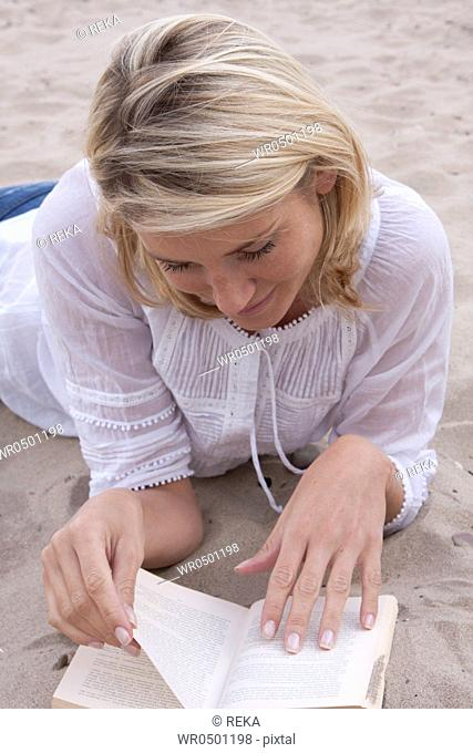 Blond woman reading book in sand