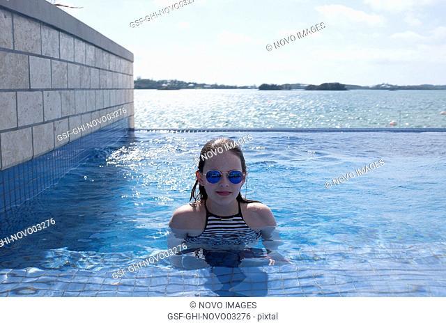 Portrait of Girl in Sunglasses in Infinity Pool