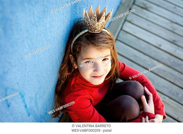 Portrait of little girl with a crown leaning against blue wall looking up to camera