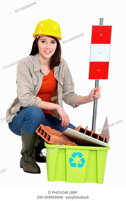 Female builder kneeling by recycle box