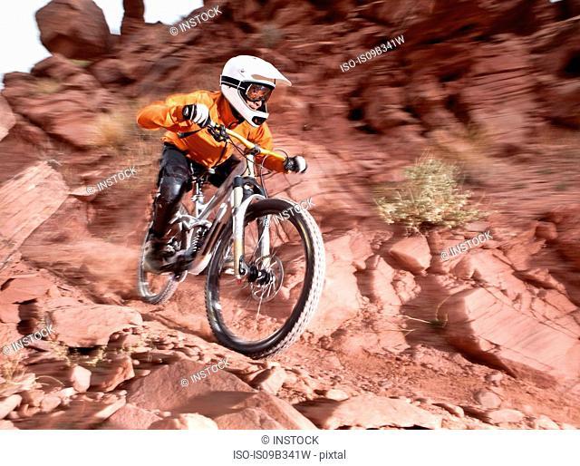 Young male downhill mountain biker speeding down muddy dirt track, Utah, USA