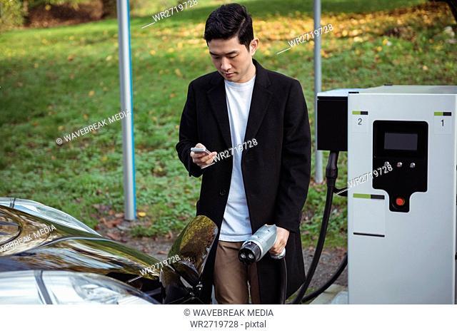 Man using mobile phone while charging car