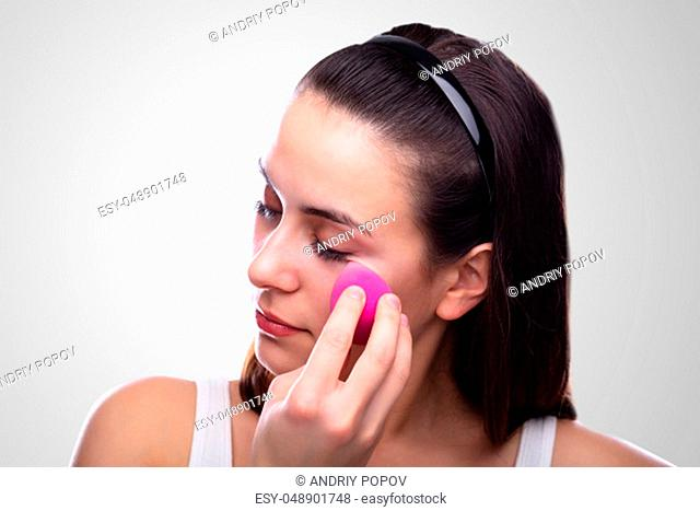 Beautiful Young Woman Applying Makeup Using Pink Blender Sponge