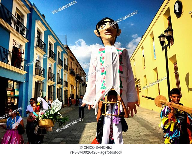 A man carries a giant paper mache doll in a street of Oaxaca, Mexico