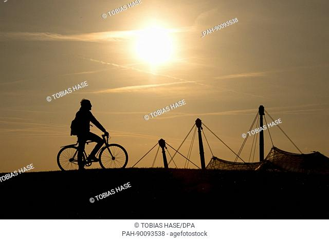 A man rides his bike while the top of the Olympic Stadium can be seen behind him in Munich, Germany, 23 April 2017. The sun came out in the late afternoon in...