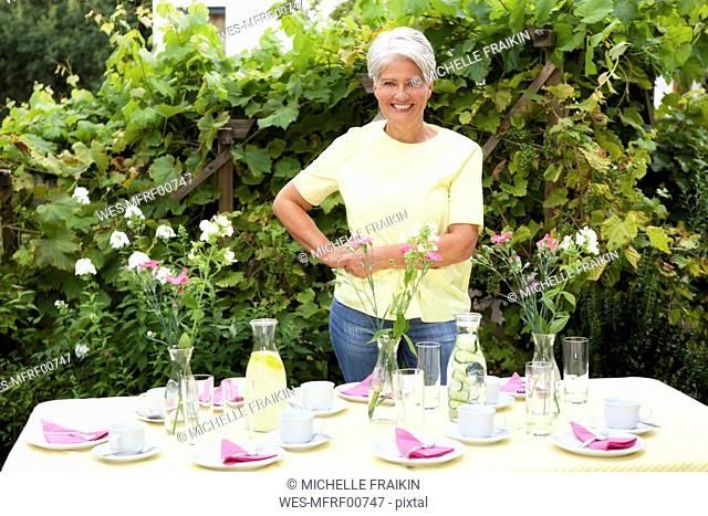 Mature woman decoration garden table for birthday party