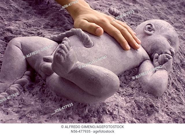 Hand touching a stone baby