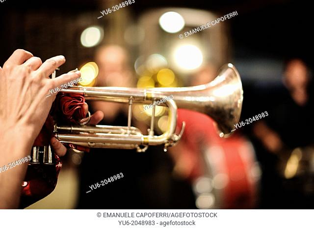 The hands of a musician as he plays the trumpet