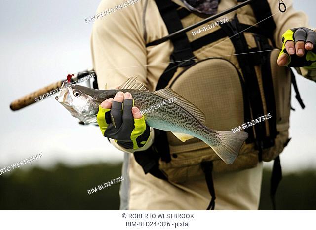 Caucasian man holding fishing rod and fish