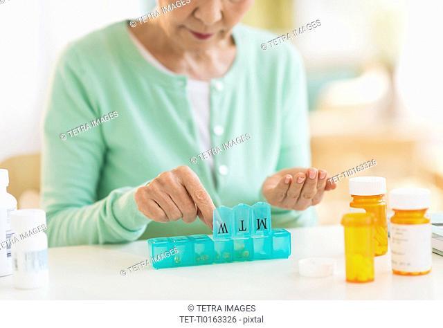 Senior woman organizing medicine in box