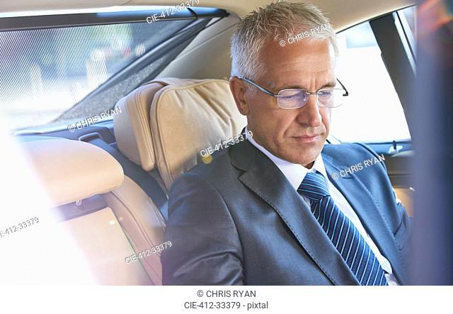 Businessman riding in back seat of town car