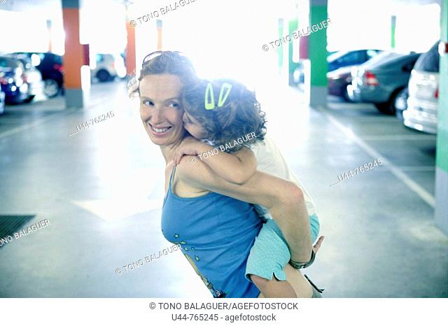 Woman holding her daughter in a car parking