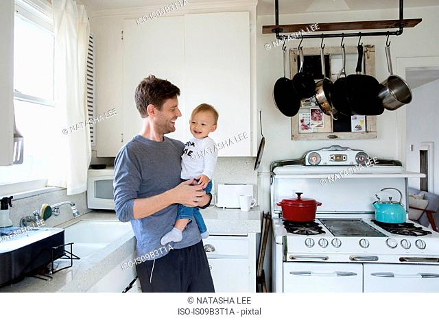 Father and young son in kitchen, father holding, laughing