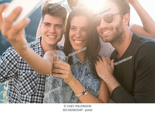Young adult friends taking selfie at roof terrace party