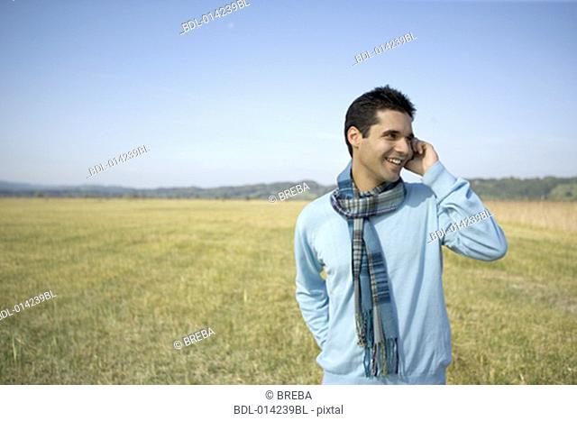 young man standing in autumnal landscape using mobile