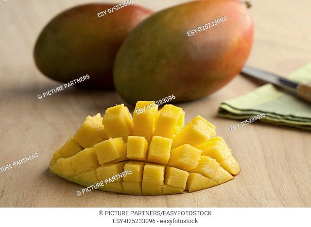 Fresh ripe juicy half yellow mango and whole in the background
