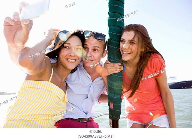 Three young friends on yacht photographing themselves