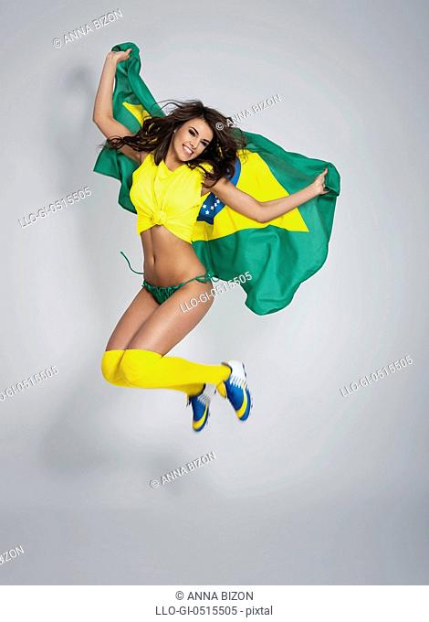 Excited jumping woman with brazilian flag. Debica, Poland