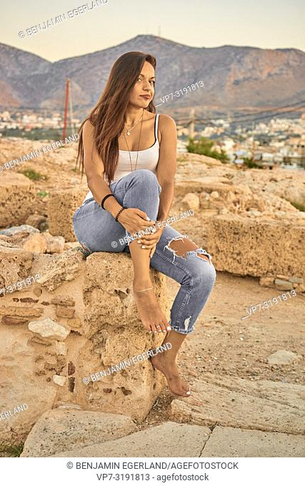 portrait of woman sitting on ancient ruins, sunset, in Chersonissos, Crete, Greece