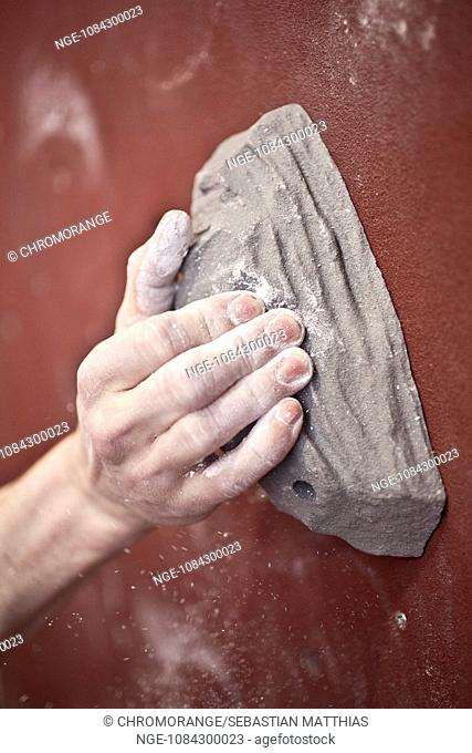 Climbers hand on a grip in a climbing hall, with chalk dust and red backround