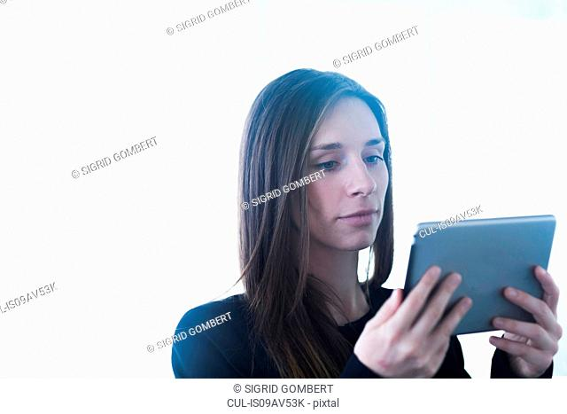 Head and shoulders of young woman using digital tablet