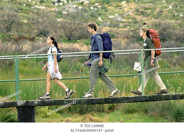 Hikers walking across footbridge