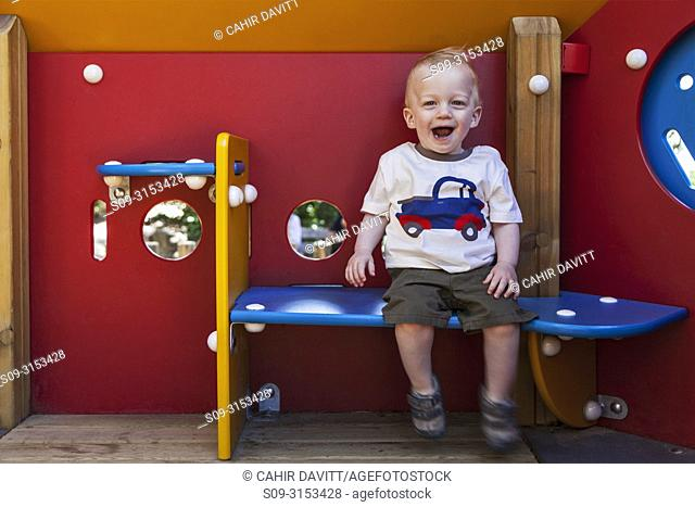 A happy 1 year old boy sits in a playground house in the suberb of El Carmel, Barcelona, Cataluna, Spain