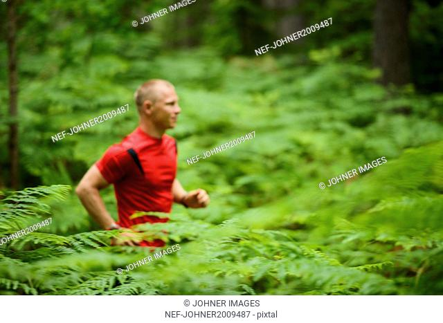 Young man running through forest